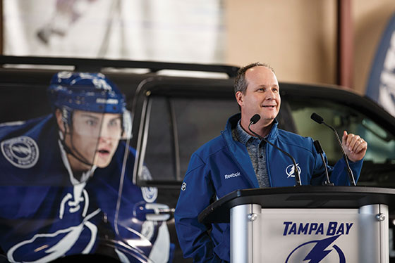 Steve Griggs speaking at a podium with a Tampa Bay Lightning vehicle behind