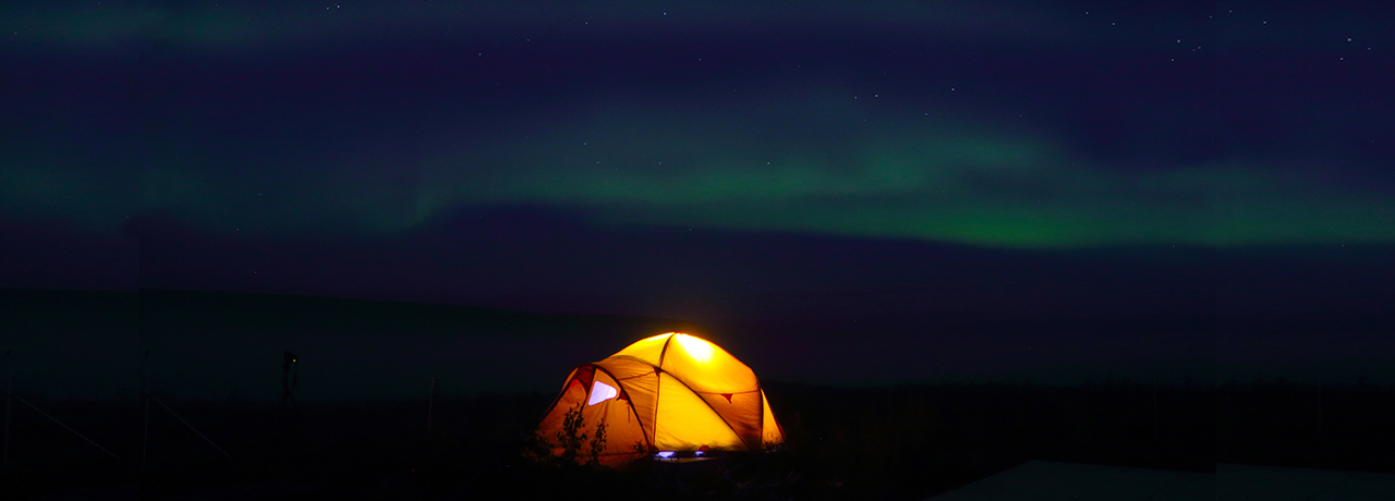 Yellow tent in aurora borealis